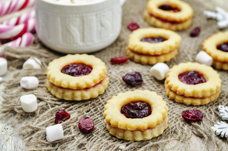Shortbread cookies with cranberry jam on a wood background. toning. selective focus Stock Photo