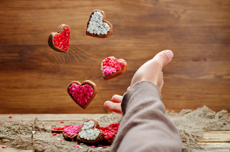 Male hand with flying cookies in the forms of hearts. toning. selective focus Stock Photo
