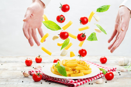 Mens hands with flying pasta with tomato and basil. toning. selective focus
