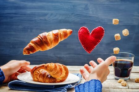 Male hand with flying croissant, toy heart and coffee on a wood background. toning. selective focus Stock Photo