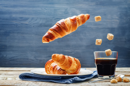 Flying croissant with coffee on a wood background. toning. selective focus Stock Photo