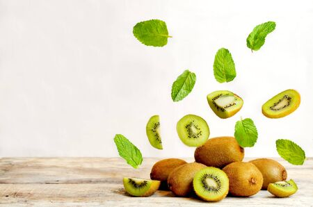 field mint: kiwi with flying slices on a wood background. tinting. selective focus Stock Photo