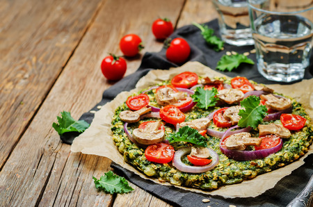 pizza crust: Kale oats pizza crust with tomato, red onion and mushrooms. toning. selective focus