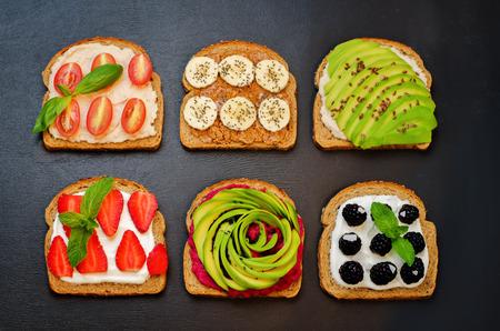 Variación de sandwiches saludables de desayuno de centeno con aguacate, hummus y bayas. viraje. enfoque selectivo