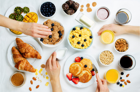 Breakfast table setting with flakes, juice, croissants, pancakes and fresh berries. toning. selective focus Stock Photo
