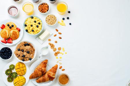 Mesa de desayuno con escamas, jugo, cruasanes, panqueques y bayas frescas. viraje. enfoque selectivo Foto de archivo - 76064240