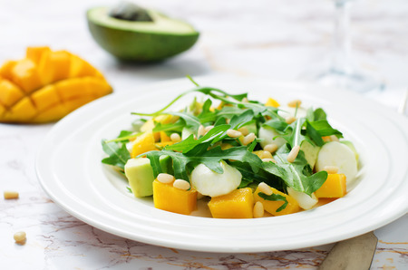 Avocado mango arugula pine nuts Mozzarella salad. toning. selective focus Stock Photo