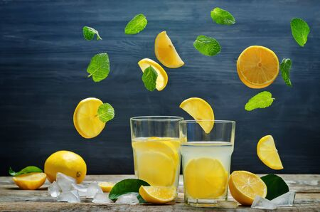 Lemonade with flying lemon, mint and ice. toning. selective focus