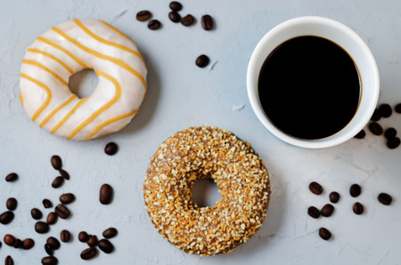 Coffee with donuts on a grey stone background. toning. selective focus