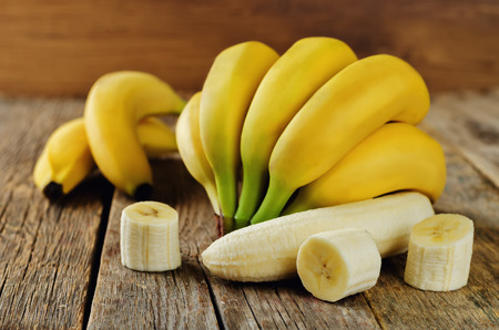 Banana with slices on a wood background. toning. selective focus