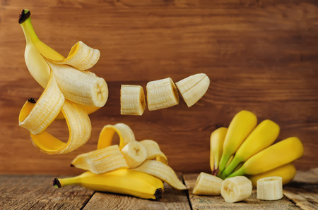 Banana with flying slices on a wood background. toning. selective focus Stock fotó - 80181221