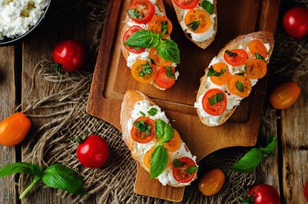 Ricotta tomato Basil bruschetta on a dark background. toning. selective focus