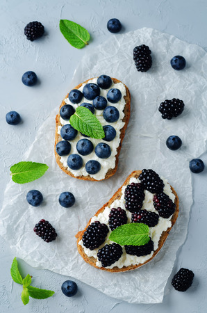 Blackberry and blueberry ricotta rye sandwiches. toning. selective focus