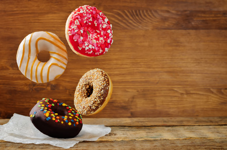 Flying donuts on a wood background. toning. selective focus