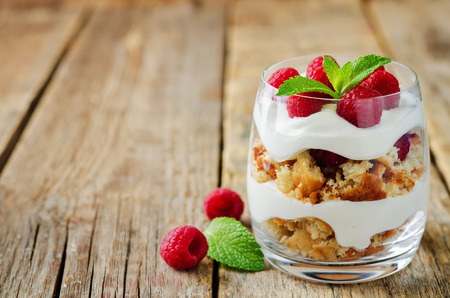 Greek yogurt raspberry biscuit parfait on a wood background. toning. selective focus