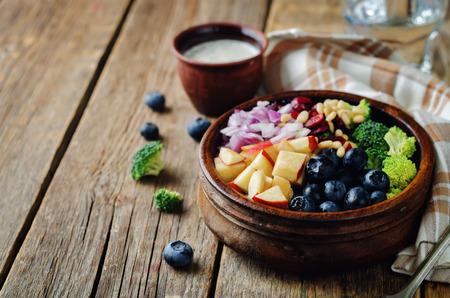 Broccoli blueberry apple salad with greek yogurt poppy seeds dressing. toning. selective focus