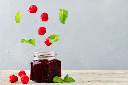 raspberry jam with flying mint and fresh raspberries. toning. selective Focus Stock Photo
