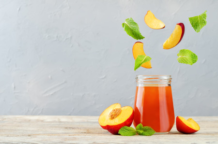 Peach jams with flying fresh peach slices and mint. toning. selective Focus