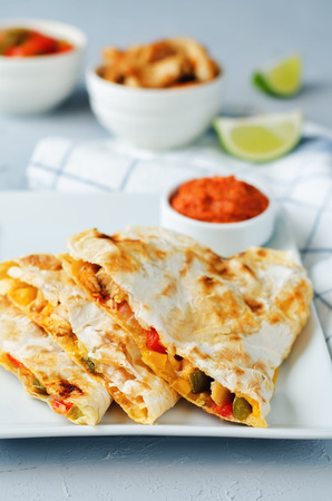 Chicken Bell pepper quesadilla on a grey background. toning. selective focus