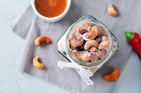 蜂蜜赤唐辛子は、灰色の背景にカシュー ナッツをローストしました。調子を整えます。選択と集中