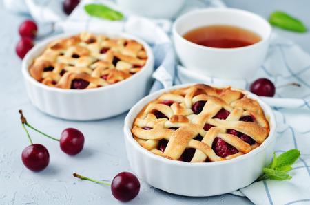 灰色の背景に新鮮なさくらんぼと桜のパイ。tonung。選択と集中