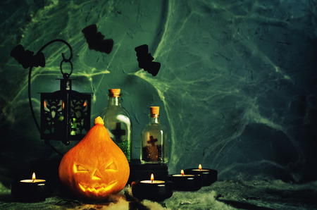 Halloween horror background with a spiders web, pumpkin; candles, potions and bats. Space for your holiday text on Halloween