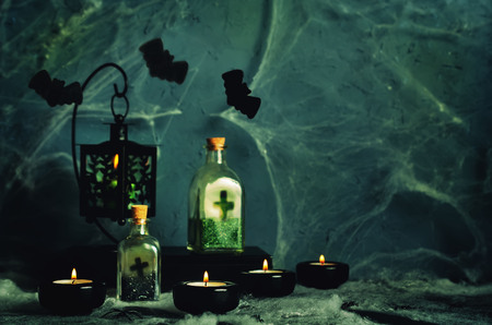 Halloween horror background with a spiders web, candles, potions and bats. Space for your holiday text on Halloween