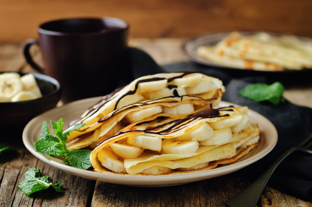 Crepes with banana on a wood background. toning. selective focus