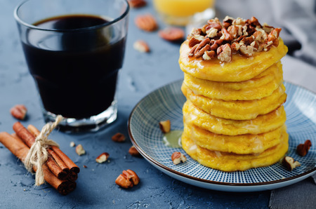 Pumpkin pancakes with pecans on a stone background. toning. selective focus