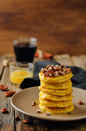 Pumpkin pancakes with pecans on a wood background. toning. selective focus