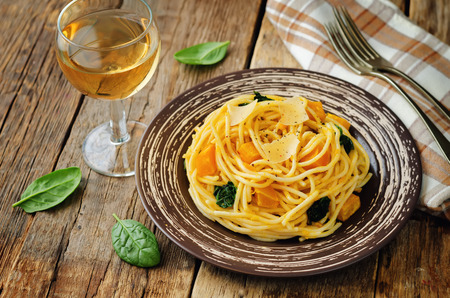 Pasta with pumpkin and spinach on a wood background. toning. selective focus Stock fotó