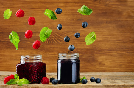 raspberry and blueberry jams with flying slices. toning. selective Focus