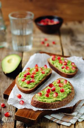 Smashed avocado pomegranate rye sandwiches. toning. selective focus