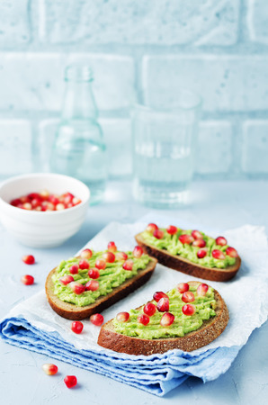 Smashed avocado pomegranate rye sandwiches. toning. selective focus