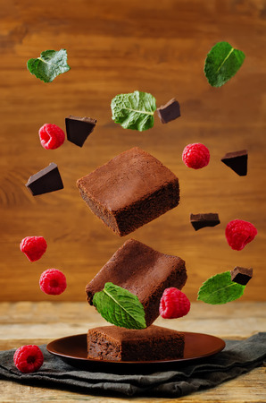 Flying Chocolate cake Brownie with mint and raspberries. toning. selective focus