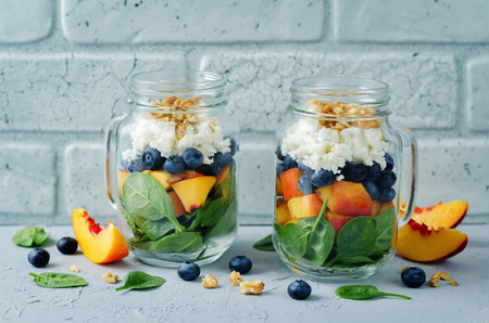 Spinach peach blueberry goat cheese walnuts salad in a jar. toning. selective focus