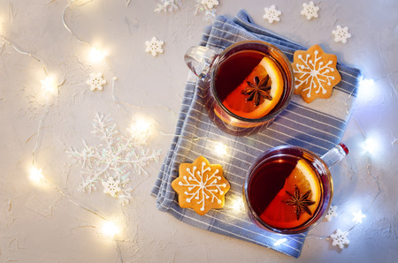 Mulled wine with gingerbread cookies and Christmas light on a grey stone background. toning. selective focus