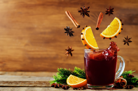 Mulled wine with flying ingredients to prepare it on a wood background. toning. selective focus