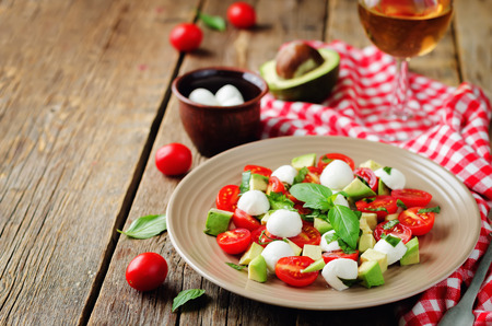 Avocado mozzarella tomato Basil salad. toning. selective focus