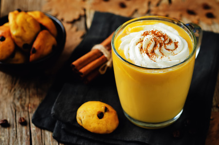 Pumpkin spice latte with whipped cream and pumpkin chocolate chips cookies. toning. selective focus