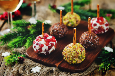 Variation of goat cheese balls appetizer with pistachio, pomegranate and flax seeds. toning. selective focus
