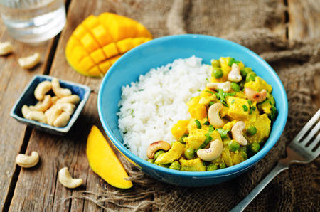 Mango chicken coconut curry with rice on a wood background. toning. selective focus Stock Photo