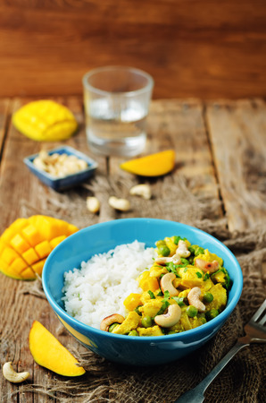 Mango chicken coconut curry with rice on a wood background. toning. selective focus Reklamní fotografie