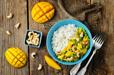 Mango chicken coconut curry with rice on a wood background. toning. selective focus 版權商用圖片