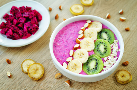 Pitaya banana smoothie bowl on a wood background. toning. selective focus 版權商用圖片
