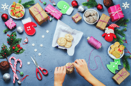 Christmas background with gifts, cookies, Christmas decoration and woman's hands holding cookies. toning. selective focus Stock Photo - 90081495