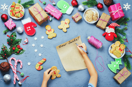 Christmas background with gifts, cookies, Christmas decoration and childrens hands writing a letter to Santa Claus. toning. selective focus