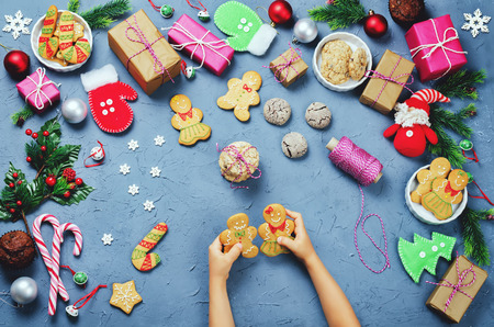 Christmas background with gifts, cookies, Christmas decoration and childrens hands holding gingerbred cookies. toning. selective focus