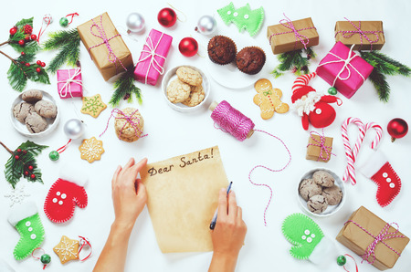 Christmas background with gifts, cookies, Christmas decoration and womans hands writing a letter to Santa Claus. toning. selective focus