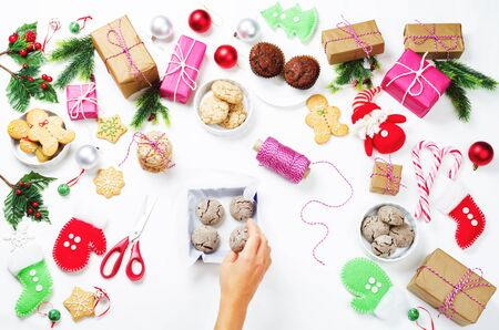 Christmas background with gifts, cookies, Christmas decoration and womans hands holding cookies. toning. selective focus Stock Photo